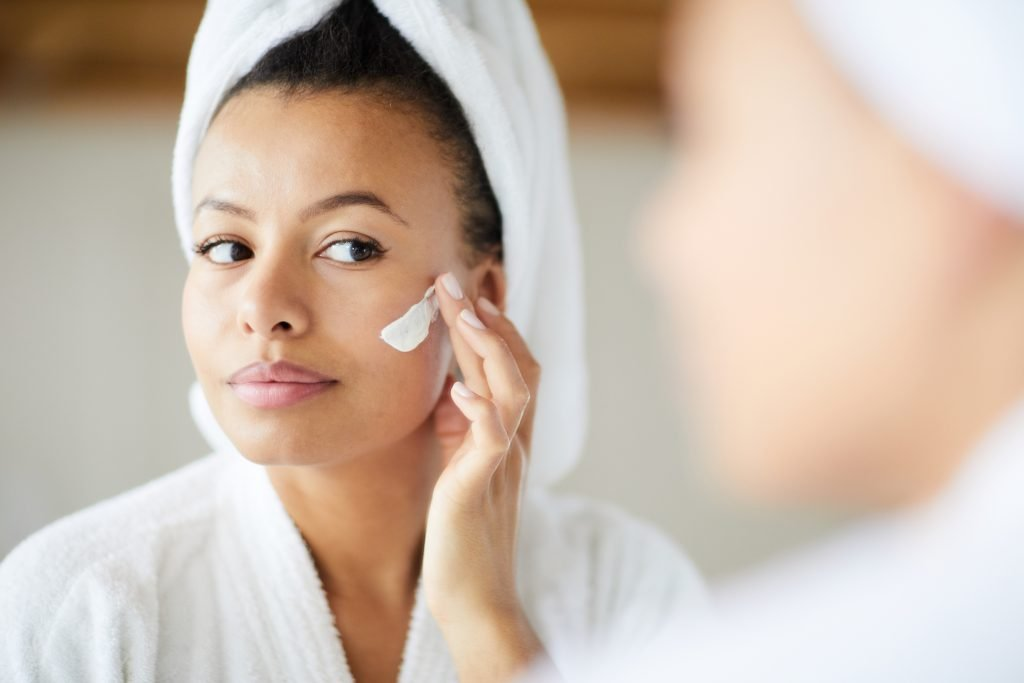 Head and shoulders portrait of beautiful Mixed-Race woman applying face cream during morning routine, copy space