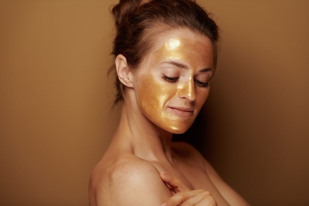 Portrait of modern middle age woman with golden cosmetic face mask on bronze background.