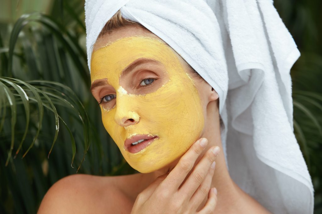 Beauty Mask. Woman In Bath Towel On SPA Procedure Close Up Portrait. Face Covered With Yellow Skin Care Product For Oil Derma. Anti-Aging Therapy At Tropical Resort.