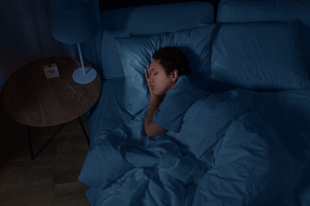 people, relax and comfort concept - young african american woman sleeping in bed at home at night