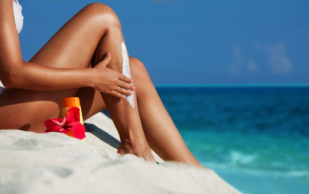 Applying sunscreen on the skin at the beach